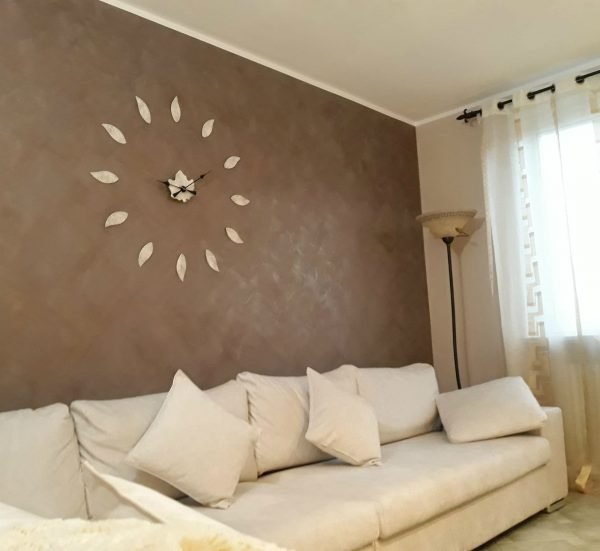 orologio grande su parete tortora dietro divano
