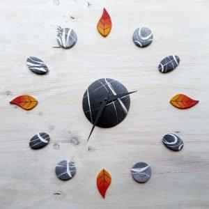 orologio da parete particolare con pietre e foglie