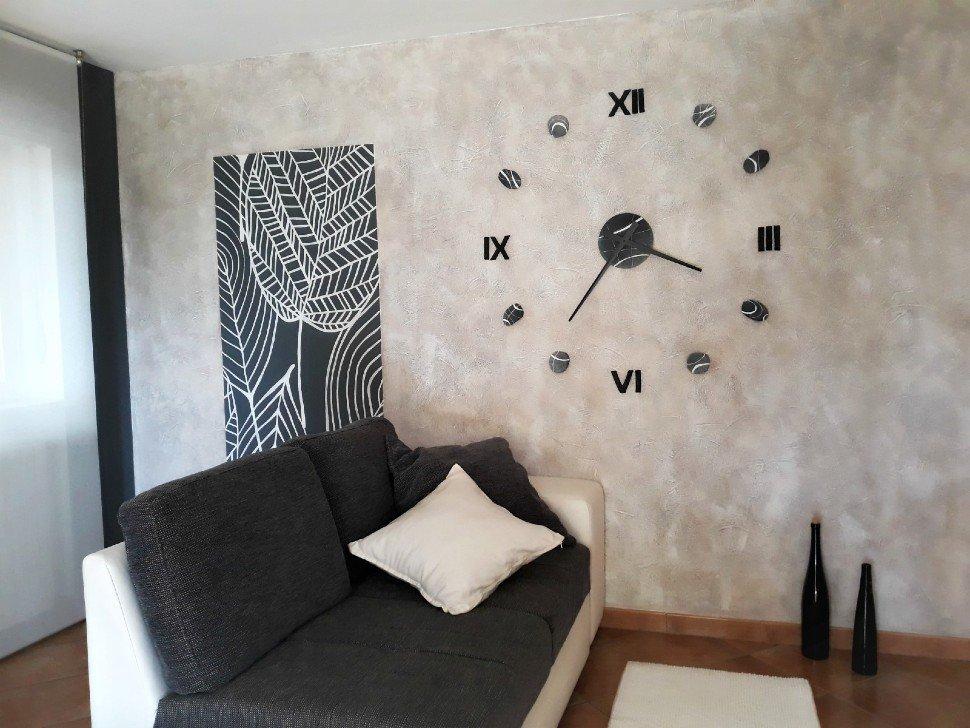 parete spatolata beige con orologio adesivo